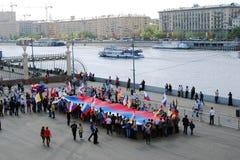 La gente tiene una bandiera russa e fa una pausa il fiume di Mosca. Immagine Stock