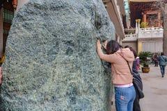 La gente tocca la grande pietra di spirito in jian una porcellana della città di Schang-Hai del tempio immagini stock libere da diritti