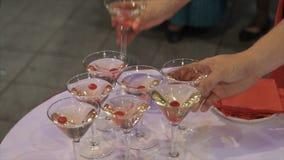 La gente toma de la tabla al vidrio de Martini y de whisky Champán en vidrios con la cereza fresca en la tabla y el partido Imágenes de archivo libres de regalías