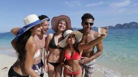La gente toma la foto de Selfie en el teléfono elegante de la célula en la playa, grupo joven sonriente feliz de los turistas el  almacen de metraje de vídeo