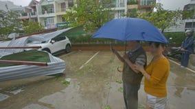 La gente toma los tejados rotos las fotos en los automóviles después de huracán