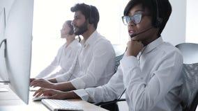 La gente trabaja en el centro del contacto Mujer en el funcionamiento de las auriculares metrajes