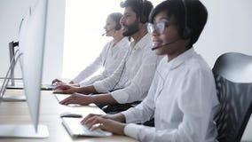 La gente trabaja en el centro del contacto Mujer en el funcionamiento de las auriculares almacen de video