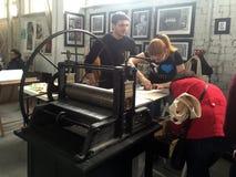 La gente trabaja en la impresora vieja en taller del arte foto de archivo
