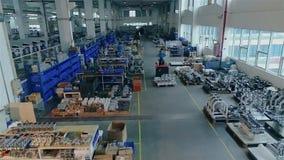 La gente trabaja en una fábrica moderna grande, el interior es una fábrica moderna grande El hombre en el cargador lleva el artíc metrajes