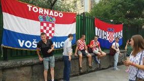 La gente trafica delante de banderas nacionales croatas del equipo de fútbol almacen de video