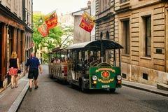 La gente in tram di escursione alla via con le bandiere a Ginevra Immagini Stock Libere da Diritti