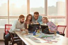 La gente in ufficio che guarda i video divertenti sul computer portatile Fotografie Stock