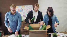 La gente in ufficio che mette immondizia di plastica nel recipiente di riciclaggio stock footage
