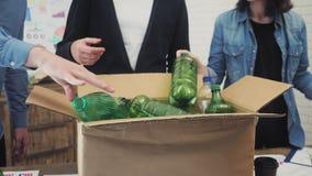La gente in ufficio che mette immondizia di plastica nel recipiente di riciclaggio archivi video