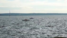 La gente in una barca che galleggia sul lago stock footage