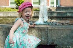 La gente Una piccola bambina sveglia in un vestito sta tenendo le sue mani sopra una fontana e una risata Immagini Stock