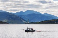 La gente in una piccola barca a vela davanti al piccolo villaggio di Ullapool negli altopiani in Scozia Immagini Stock Libere da Diritti