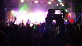 La gente utiliza el vídeo de registro de los teléfonos elegantes en el concierto de la música almacen de video