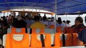 La gente va dal mare sul traghetto e si siede sui sedili Vista interna thailand stock footage