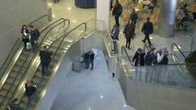 La gente va su una scala mobile, in un centro commerciale Fanno gli acquisti, camminano e riposano la vista da sopra stock footage