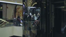 La gente va sull'elevatore al centro commerciale archivi video
