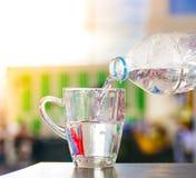 La gente vertió el agua en hierba en una oficina o el hogar empañó el fondo Usando el papel pintado o el fondo para beber, natura imagen de archivo libre de regalías