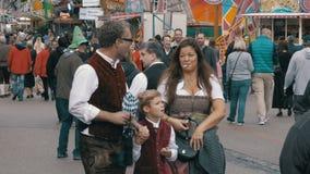 La gente in vestiti bavaresi nazionali che cammina lungo la via del festival di Oktoberfest Monaco di Baviera, Germania video d archivio