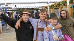 La gente in vestiti bavaresi nazionali si diverte sulla via della Baviera di Oktoberfest, movimento lento stock footage
