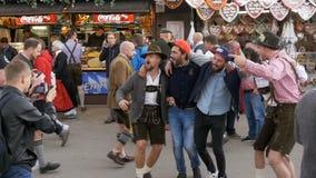 La gente in vestiti bavaresi nazionali si diverte sulla via della Baviera di Oktoberfest, movimento lento archivi video