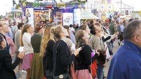 La gente in vestiti bavaresi nazionali sulla via del festival di Oktoberfest La Baviera, movimento lento stock footage