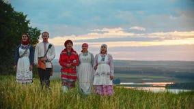 La gente in vestiti pieghi tradizionali che cammina sul campo e che canta una canzone archivi video
