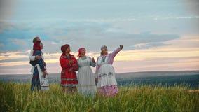 La gente in vestiti pieghi tradizionali che stanno sul campo e che prendono un selfie archivi video
