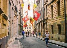 La gente in via con le bandiere sull'hotel Ville a Ginevra Fotografie Stock