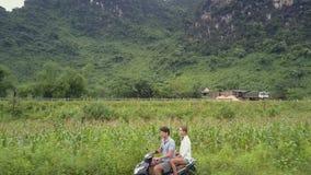 La gente viaja en la vespa en el sitio rural cerca de la antena de la montaña almacen de metraje de vídeo