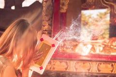 La gente viene rogar con los palillos de ídolo chino que queman en un templo budista del vintage como ofrecimiento durante Año Nu fotografía de archivo libre de regalías