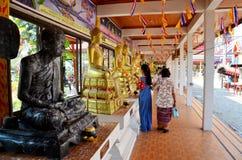 La gente vierte el agua sobre un Buda que las imágenes son un gesto de la adoración Imagenes de archivo