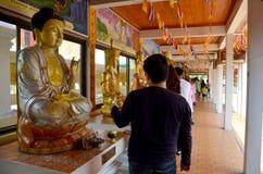 La gente vierte el agua sobre un Buda que las imágenes son un gesto de la adoración Imagen de archivo