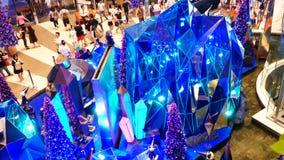 La gente visita la decoración del festival de la Navidad y de la demostración del punto culminante en el centro comercial de Siam