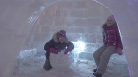 La gente y el bebé caminan en ciudad del hielo durante las nevadas Juegos de niños en el iglú en la ciudad del hielo, pueblo de l
