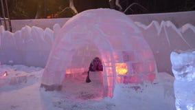 La gente y el bebé caminan en ciudad del hielo durante las nevadas Juegos de niños en el iglú en la ciudad del hielo, pueblo de l Fotos de archivo libres de regalías