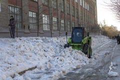 La gente y el cargador verde de la quitanieves quita nieve de las calles de la ciudad imágenes de archivo libres de regalías