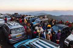 La gente y los coches están viendo la primera luz del día del ` s del Año Nuevo en el amanecer con los pueblos de montaña y la mo Fotos de archivo