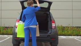 La gentille et sûre femme marche dans le parking à sa voiture Elle s'inquiète des paniers La fille ouvre le tronc et le met là clips vidéos