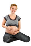 La gentille femme enceinte souriant et caressent son ventre Images libres de droits