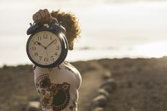 La gentille femme prennent à une grande alarme d'horloge le vieil et le cru en main te montrant les minutes et les secods précipi photographie stock