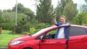 La gentille femme se tient en dehors de la voiture et regarde sur l'appareil-photo Elle pose La fille tient des clés et les ondul clips vidéos