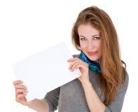 La gentille femme tient la page du papier blanche Photographie stock