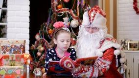 La gentille fille assez blonde avec un arc rose dans ses cheveux, dans une belle robe, est livre de lecture avec le père de Santa clips vidéos
