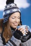 La gentille fille buvant du thé chaud dans des yeux de l'hiver s'est fermée Photographie stock libre de droits