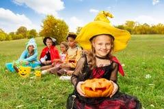 La gentille fille dans le costume de sorcière tient le potiron découpé Image libre de droits
