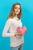 La gentille fille douce avec des baloons et les petits prersents mettent en sac dans les mains sur le fond bleu Rose rouge Hapine Photo libre de droits