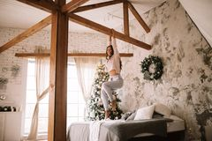 La gentille fille habillée dans le chandail et le pantalon blancs accroche sur une barre en bois au-dessus du lit avec la couvert photographie stock
