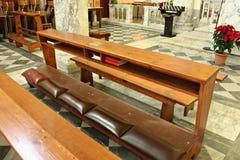 La genuflexión para fiel ruega en la iglesia fotos de archivo