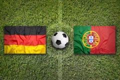 La Germania contro Bandiere del Portogallo sul campo di calcio Immagini Stock